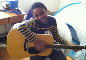 My son, Noah Collins, hanging out in his room with his guitar (Image Source: Angelia Levy, May 2014)